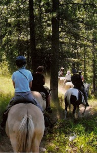 Riders winding through the woods on the trail to Coon Lake